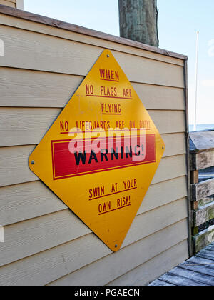 Ocean beach warning sign stating no lifeguard is on duty and to swim at your own risk when no flags are flying in Destin Florida, USA. - Stock Image