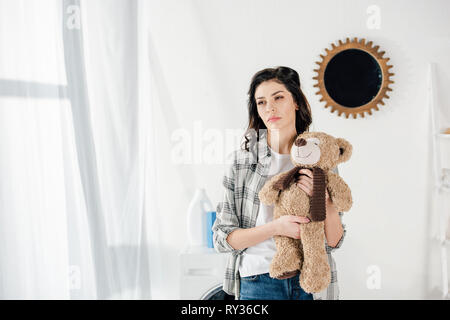 woman holding bear toy and thinking at home - Stock Image