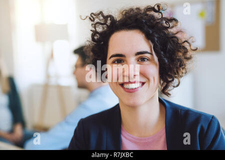 A portrait of young hipster businesswoman with colleagues in the background a modern office. - Stock Image