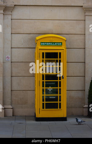 Traditional telephone box painted yellow and used for a defibrillator to be stored and accessed by the public in an emergency - Stock Image