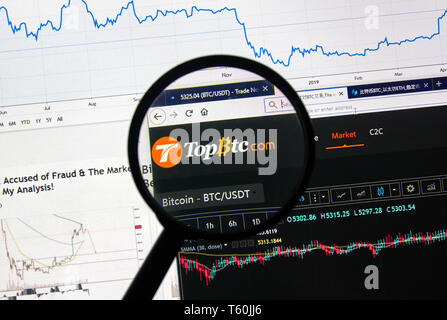 MONTREAL, CANADA - APRIL 26, 2019: TopBTC.com cryptocurrency digital assets exchange logo and home page on a laptop screen under magnifying glass. - Stock Image