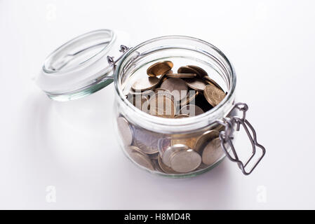 Coins in glass money jar - Stock Image