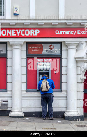 Man using MoneyCorp free cash withdrawal machine. - Stock Image