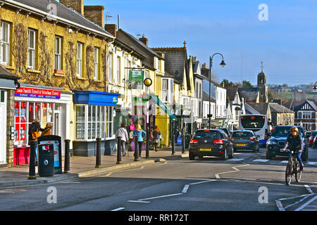 A general street view of the High Street in Cowbridge with it's eclectic mix of famous brands and small local specialist shops. Cyclist cars & buses. - Stock Image