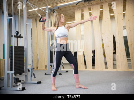 Young athletic woman doing strength exercises in the gym - Stock Image