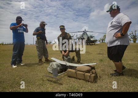 Sgt. Connor Ogara, an intelligence specialist with Alpha Company, Battalion Landing Team, 1st Battalion, 4th Marines, showcases an unmanned aerial system for residents of Tinian, Commonwealth of the Northern Mariana Islands, March 11, 2019. Marines and Sailors with Combat Logistics Battalion 31 led a multi-service task force, partnering with the Federal Emergency Management Agency, to help the U.S. citizens of Tinian begin recovery efforts in the wake of Super Typhoon Yutu last year. The Marines and Sailors, currently participating in two weeks of unit-level training on nearby Guam, visited Ti - Stock Image