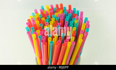 Colorful plastic drinking straws held together against a neutral background. One use, made of plastic straws, number one reason of oceans pollution - Stock Image