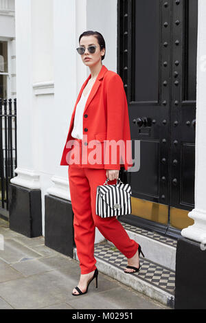 Chic young woman in red suit leaving smart London house - Stock Image