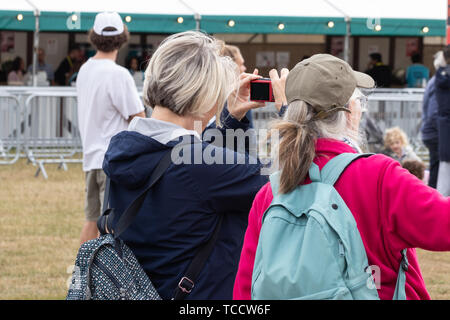 Two middle aged women stood together at a festival, one of the women is taking a photo with her mobile phone or cell phone - Stock Image