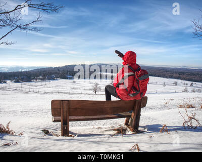 Side view of man walking in snow on winter day, mountain landscape. Hiker in red with  red backpack. Winter hiking travel concept. - Stock Image