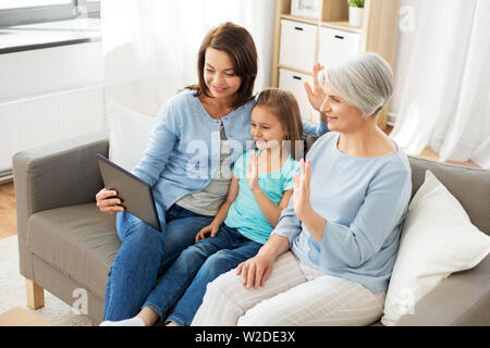 mother, daughter and grandmother with tablet pc - Stock Image