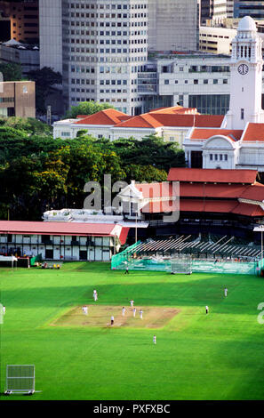 Cricket being played on The Padang, Singapore with financial district and clock tower in the background. - Stock Image