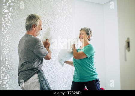 Happy cheerful old senior caucasian couple play at home with pillows in the bedroom - playful and youthful concept with no limit age to have fun and l - Stock Image