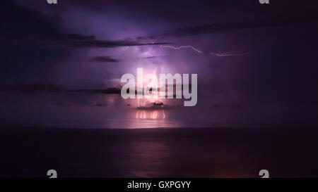 Purple lightning over the sea, powerful thunderbolt, amazing night landscape, stormy weather in the sea - Stock Image