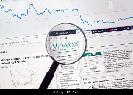 MONTREAL, CANADA - APRIL 26, 2019: VirWox cryptocurrency digital assets exchange logo and home page on a laptop screen under magnifying glass. - Stock Image