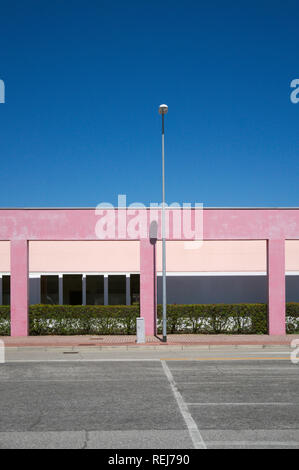 an empty parking lot with lamppost and an unfinished shopping mall - Stock Image