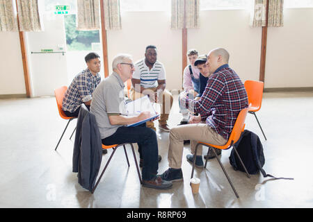 Men talking in circle in group therapy - Stock Image