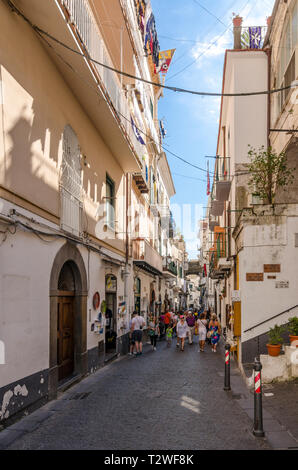 Tourists and holiday makers walking down a narrow street in Amalfi, Italy - Stock Image