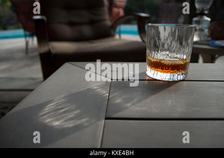 A small glass with Disarrono liquor sits on a wooden table while sunlight filters through the glass, making a pattern - Stock Image