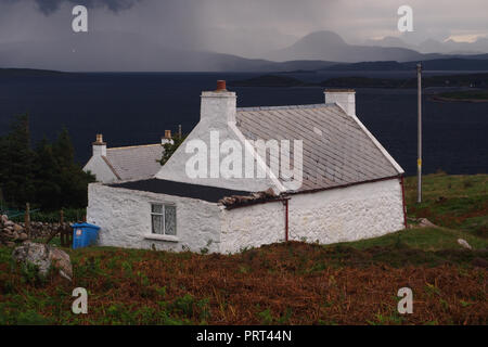 A view of a small white croft house in Polbain, Scotland with the Summer Isles out in the sea and mountain ranges in the far distance - Stock Image