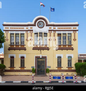 Facade of Financial Affairs Department of Suez Canal Authority with yellow bricks, Single door, windows covered with iron bars, and clock - Stock Image