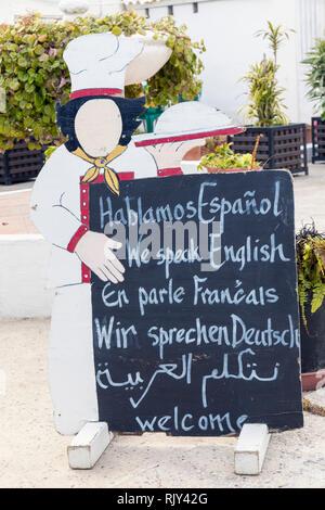Multilingual restaurant sign. We speak Spanish, English, French, German, Arabic. - Stock Image