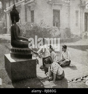 Four young women giving flower offerings to Buddha, French Indochina. - Stock Image
