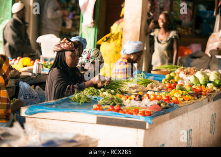 Indigenous Jola Karon women sell produce at a market in Senegal, West Africa. - Stock Image