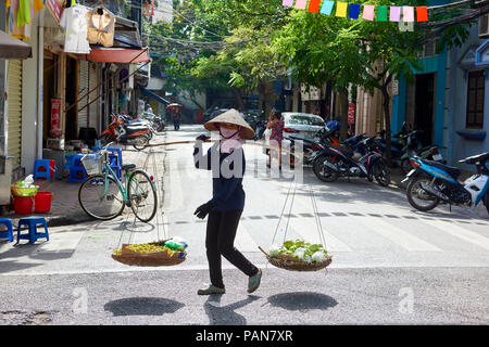 A woman carrying her merchandise in baskets balanced on her shoulder in Hanoi, Vietnam, wearing a traditional conical hat. Women selling products on t - Stock Image