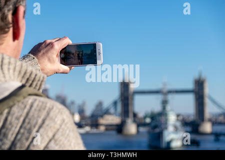 Man taking a photo of Tower Bridge on a mobile smart phone. London February 2019 - Stock Image