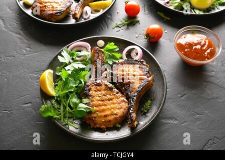 Tasty grilled pork steaks on plate over black stone table - Stock Image