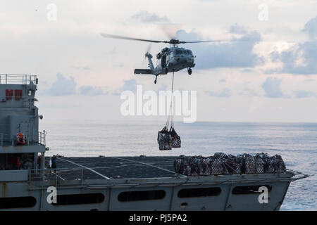 180824-N-TT202-076  ATLANTIC OCEAN (Aug. 24, 2018) An MH-60S Sea Hawk from the Dusty Dogs of Helicopter Sea Combat Squadron (HSC) 7 transports cargo from the fast combat support ship USNS Arctic (T-AOE 8) to the Nimitz-class aircraft carrier USS Abraham Lincoln (CVN 72) during a replenishment-at-sea. Abraham Lincoln is currently underway conducting carrier qualifications. (U.S. Navy photo by Mass Communication Specialist 3rd Class Daniel E. Gheesling/Released) - Stock Image
