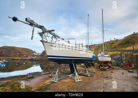 A leisure boat / yacht sitting in the harbor at Portknockie village, north of Scotland, UK. - Stock Image