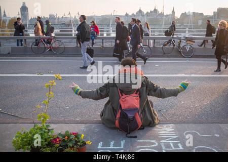 A demonstrator meditates on Waterloo Bridge for the Extinction Rebellion demonstration as people walk by - Stock Image