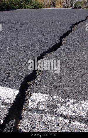 Cracks across tarmac road from earthquakes in the previous year - Stock Image