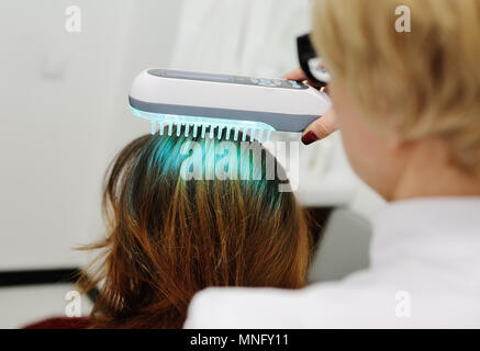 Doctor examines scalp a special device with a UV lamp - Stock Image