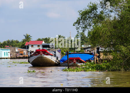Traditional Vietnamese house boats moored by stilt houses on river in Mekong Delta. Cai Be, Tien Giang Province, Vietnam, Asia - Stock Image