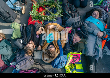 London, UK. 31st October 2018. People llie down and link arms to block the roadway in front of Parliament after making the 'Declaration of Rebellion' against the British Government for its criminal inaction in the face of climate change catastrophe and ecological collapse. They listened to speeches by George Monbiot and Green Party MP Caroline Lucas and there were songs and poems. A number of activists brought large wreaths and lay down with them, with several lock-ons. Police tried to clear the road, but the protesters ignored them, taking a show of hands to remain blocking the road for anoth - Stock Image