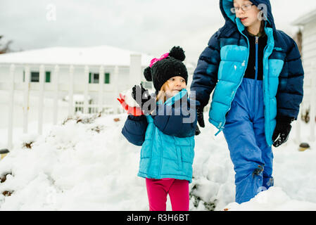 Siblings, a boy and a girl, play in the snow on a cold winter day in the United States. - Stock Image