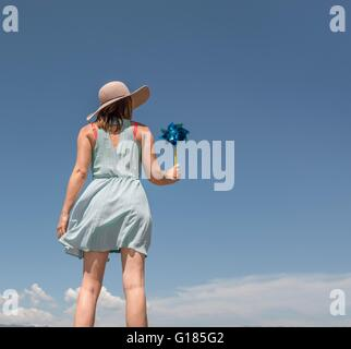 Rear view of woman with hat holding paper windmill - Stock Image