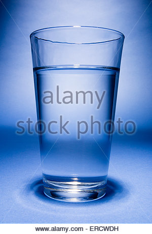 Glass of water on blue background - Stock Image