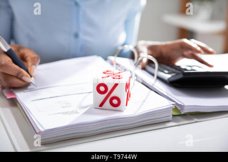 Close-up Of White Block With Percentage Symbol While Businessperson Calculating Invoice Over White Desk - Stock Image