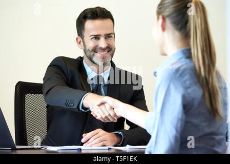 Businessman shaking hands with businesswoman in office - Stock Image