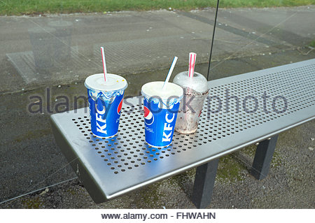 Fast food litter from KFC - single use paper cups left on a bench in a bus stop waiting shelter. Newport, Wales, - Stock Image