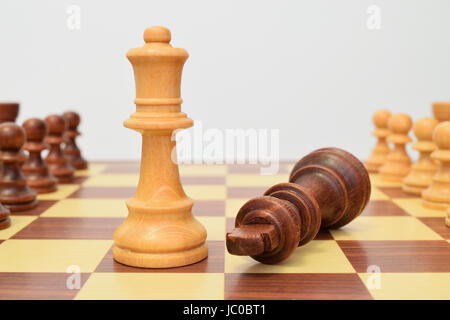 King at the queen's feet on the chessboard - Stock Image