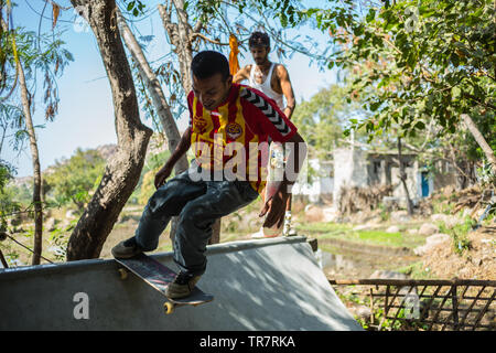 Co-funder of Holystoked Skateboarding, Shake, is skating on a mini ramp in Hampi, India. - Stock Image