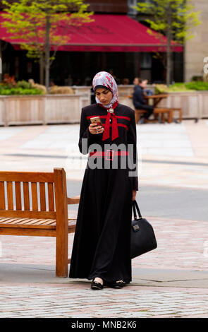 A Turkish Muslim woman wearing a black and red Abaya dress texting messages on her iPhone in Dundee city centre, UK - Stock Image