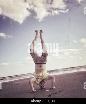 Guy doings handstand on beach, Isle of Palms, South Carolina - Stock Image