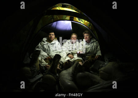 A U.S. Marine assigned to The Combined Arms Company out of Bulgaria, prepare for bed after a long day of walking. - Stock Image