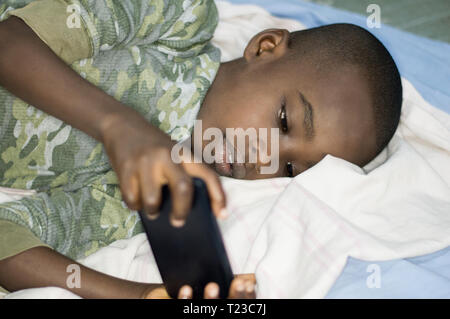 Child boy handling a mobile phone lying in bed - Stock Image